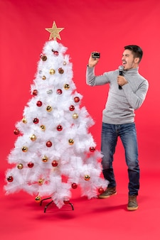 L'humeur de noël avec un gars confiant habillé en jeans debout près de l'arbre de noël décoré et tenant une vidéo de tournage de microphone
