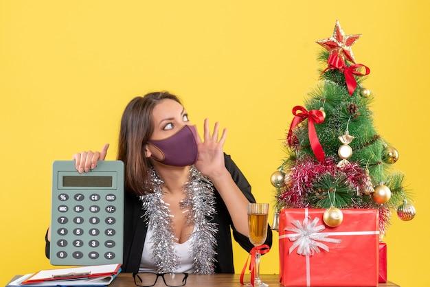 L'humeur de noël avec grave belle dame en costume portant un masque médical tenant calculatrice au bureau sur jaune