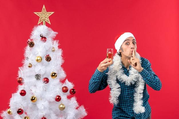 L'humeur de noël avec heureux jeune homme émotionnel fou avec chapeau de père noël dans une chemise dépouillé bleu soulevant un verre de vin faisant le geste de silence près de l'arbre de noël