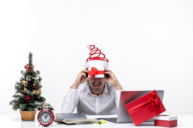 Humeur de noël avec homme d'affaires drôle avec chapeau de père noël tenant son cadeau devant son visage et sortant sa langue sur fond blanc
