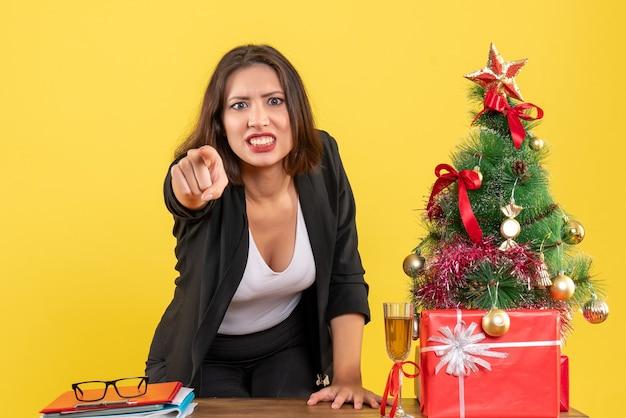 L'humeur de noël avec jeune femme d'affaires émotionnelle en colère tendue nerveuse montrant quelque chose sur le jaune