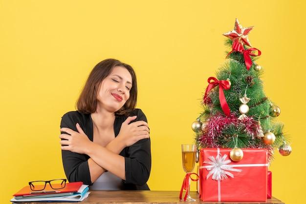 Humeur de noël avec jeune femme d'affaires émotionnelle souriante satisfaite rêvant de quelque chose sur jaune