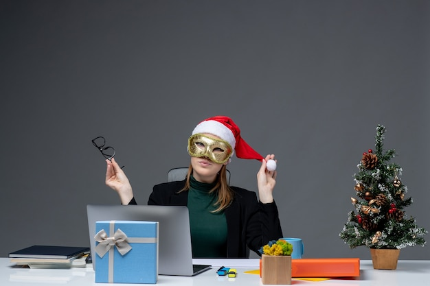 L'humeur de noël avec jeune femme jouant avec chapeau de père noël tenant des lunettes et portant un masque assis à une table sur fond sombre