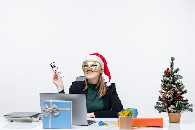L'humeur de noël avec une jeune femme positive de rêve avec chapeau de père noël tenant des lunettes et portant un masque assis à une table sur fond blanc