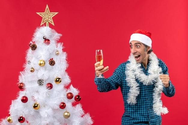L'humeur de noël avec un jeune homme émotionnel fou avec un chapeau de père noël dans une chemise rayée bleue tenant un verre de vin près de l'arbre de noël