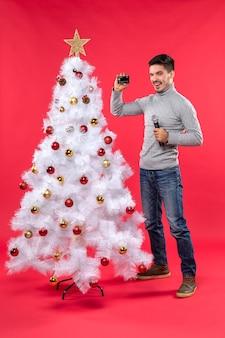 Humeur de noël avec jeune homme souriant debout près de l'arbre de noël décoré et tenant le microphone et le téléphone