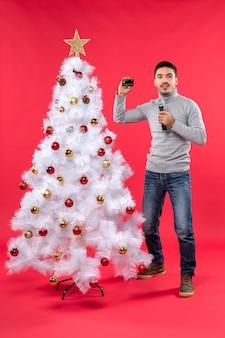 L'humeur de noël avec mec confiant debout près de l'arbre de noël décoré et tenant le microphone en prenant des photos