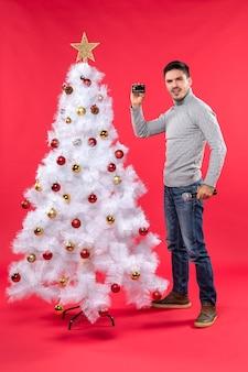 L'humeur de noël avec sérieux jeune homme debout près de l'arbre de noël décoré et tenant le microphone et le téléphone debout avec confiance