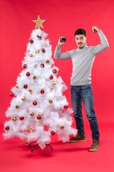 L'humeur de noël avec sérieux jeune homme debout près de l'arbre de noël décoré et tenant un microphone et un téléphone montrant son pouvoir