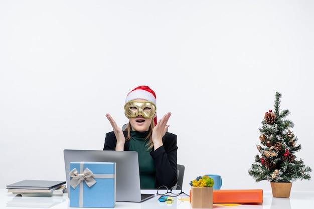 L'humeur de noël avec surpris jeune femme excitée avec chapeau de père noël et portant un masque assis à une table sur un fond blanc