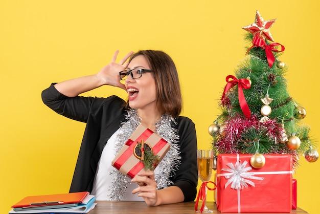 Humeur de nouvel an avec belle femme d'affaires en costume avec des lunettes et assis à une table au bureau