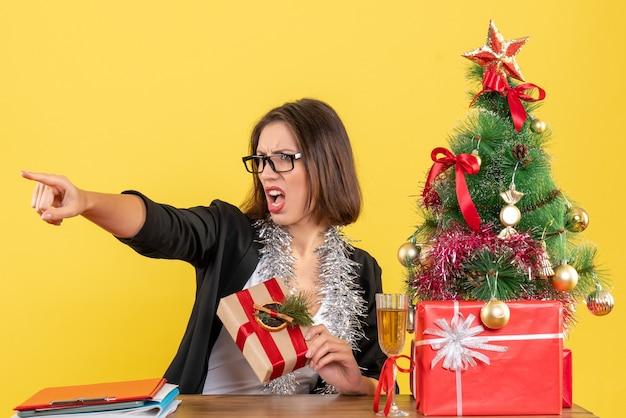 Humeur de nouvel an avec belle femme d'affaires en costume avec des lunettes pointant quelque chose et assis à une table dans le bureau