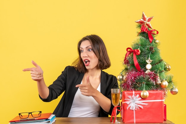 Humeur de nouvel an avec belle femme d'affaires pointant quelque chose et assis à une table au bureau