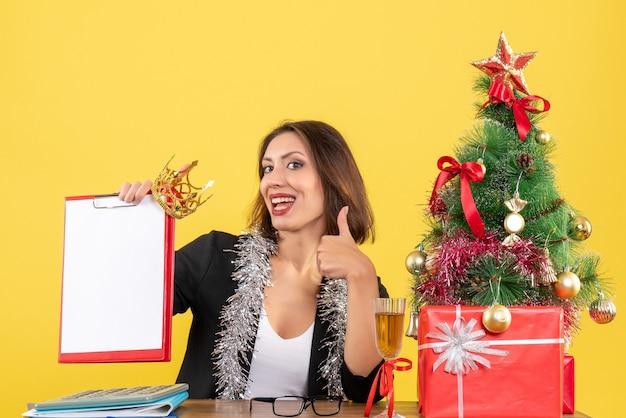 Humeur de nouvel an avec charmante dame en costume avec couronne tenant un document faisant un geste correct au bureau