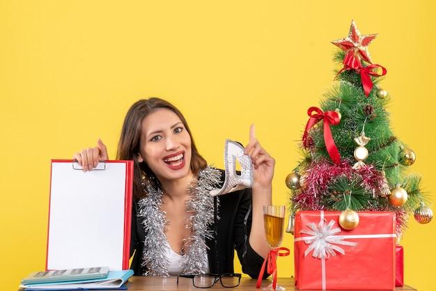 Humeur de nouvel an avec charmante dame en costume tenant un masque et montrant le document pointant vers le haut dans le bureau
