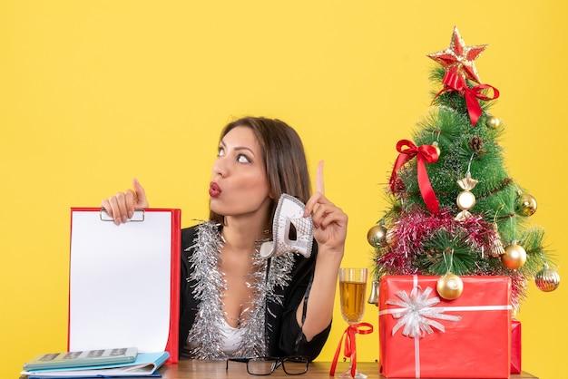 Humeur de nouvel an avec une charmante dame en costume tenant un masque et montrant un document réfléchissant profondément au bureau