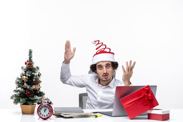 Humeur de nouvel an avec confus jeune homme d'affaires avec drôle de chapeau de père noël demandant quelque chose au bureau sur fond blanc