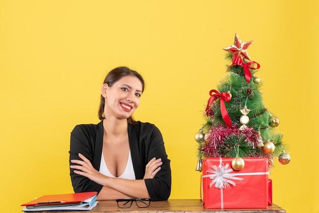 Humeur de nouvel an avec happy young woman in suit avec arbre de noël décoré au bureau sur jaune