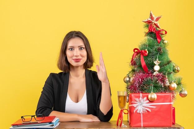 Humeur de nouvel an avec jeune femme d'affaires émotionnelle heureuse levant la main et assis à une table dans le bureau sur jaune