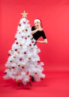 Humeur de nouvel an avec jeune femme en robe noire et chapeau de père noël debout derrière blanc