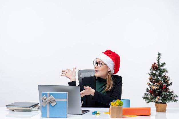 Humeur de nouvel an avec jeune femme séduisante avec un chapeau de père noël assis à une table avec un arbre de noël et un cadeau dessus et en regardant quelque chose dans le bureau