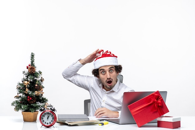 Humeur de nouvel an avec jeune homme d'affaires avec chapeau de père noël drôle regardant quelque chose de surprenant au bureau sur fond blanc