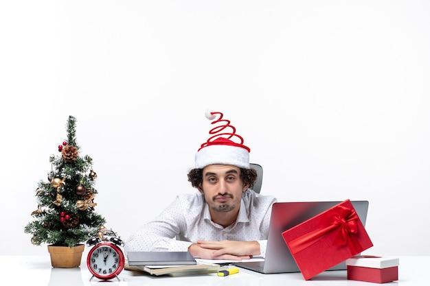 Humeur de nouvel an avec jeune homme d'affaires occupé avec drôle de chapeau de père noël se sentant épuisé de tout dans le bureau sur fond blanc