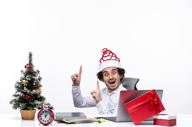 Humeur de nouvel an avec surpris souriant excité jeune homme d'affaires assis dans le bureau et pointant au-dessus sur fond blanc