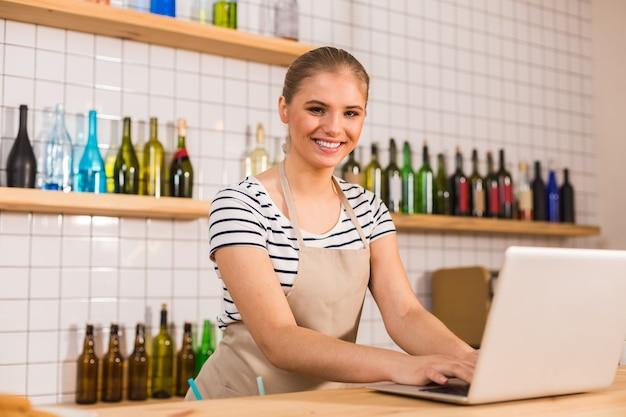 Humeur positive. belle femme positive joyeuse portant un tablier et vous souriant tout en travaillant sur l'ordinateur portable