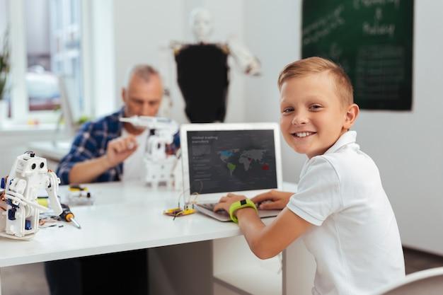 Humeur positive. joyeux garçon heureux assis devant l'ordinateur tout en vous souriant