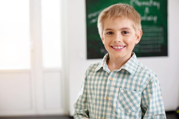 Humeur positive. joyeux garçon heureux en vous regardant tout en étant à l'école