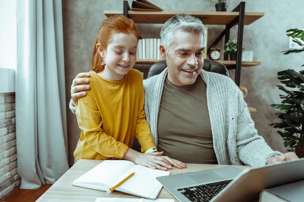 Humeur positive. joyeux père et fille sympas souriant ensemble tout en regardant l'écran de l'ordinateur portable