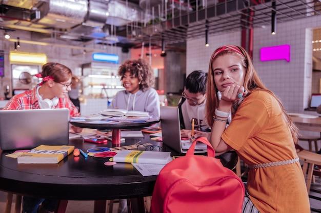 Humeur réfléchie. silhouette d'élèves heureux assis à une table ronde tout en discutant de leur tâche à domicile