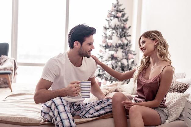 Humeur romantique. beau jeune homme barbu et une belle femme blonde en short à la romantique assis sur le lit