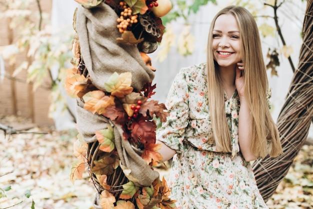 Humeur romantique. taille portrait de la jeune blonde belle femme caucasienne assise dans une grande couronne d'automne ou une balançoire et souriant à pleines dents tout en posant