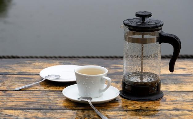 Humeur triste et mélancolique. concept de pluie et café (thé). pluie sur la véranda du café d'été, une tasse de thé solitaire.