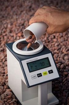 L'humidimètre mesure les niveaux d'humidité des fèves de cacao. mesurez l'humidité des fèves de cacao échantillonnées à 7%. la teneur en eau des fèves de cacao doit être de 7%.