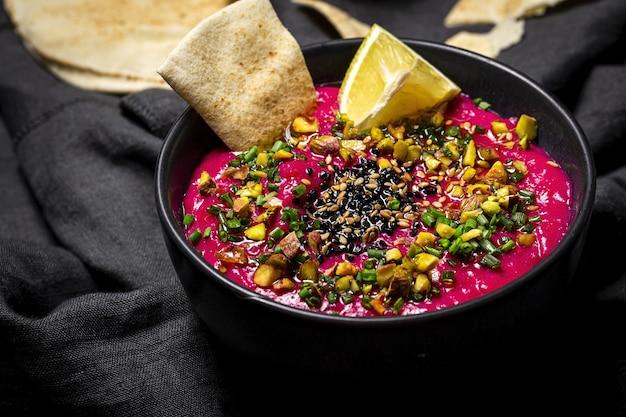 Hummus à la betterave et aux pois chiches maison avec crudités de légumes et pain sans levain sur fond sombre