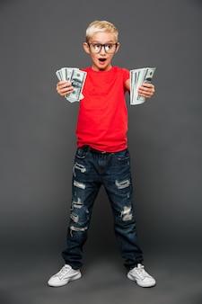 Hurlant surpris petit garçon enfant montrant de l'argent.