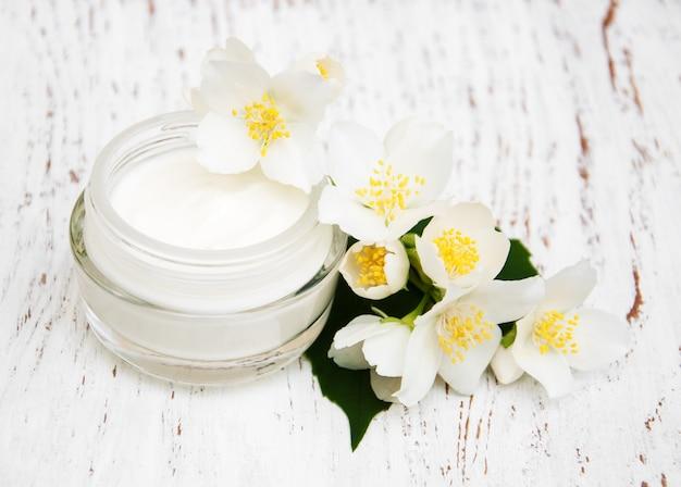 Hydratants pour le visage et le corps avec des fleurs de jasmin sur un fond en bois blanc