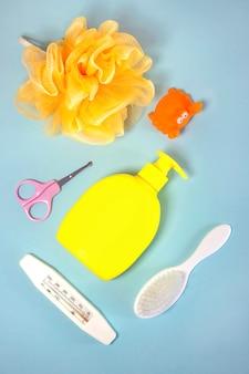 Hygiène des enfants : articles de bain, bouteille de shampoing, jouet en caoutchouc, éponge, peigne, thermomètre, vue de dessus des ciseaux de sécurité, sur fond bleu. kit de soins personnels pour enfants. accessoires de bain.