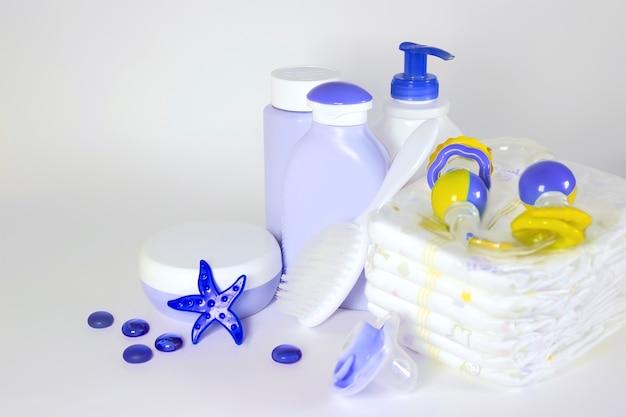 Hygiène des enfants : articles de bain, bouteille de shampoing, jouet en caoutchouc, éponge, peigne, thermomètre, vue de dessus des ciseaux de sécurité, sur fond bleu.