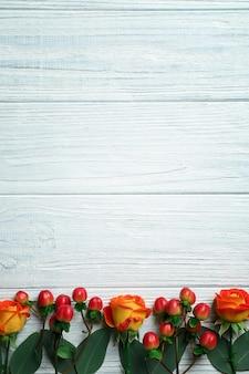 Hypericum, roses et rowan sur fond de bois blanc