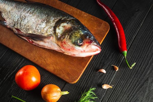 Hypophthalmichthys ou carpe à grosse tête sur une planche à découper avec des légumes avant la cuisson. poissons décortiqués crus dans une cuisine de restaurant. idée de régime de poisson