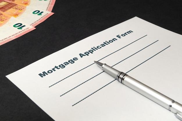 Hypothèque avec argent et stylo sur mur noir
