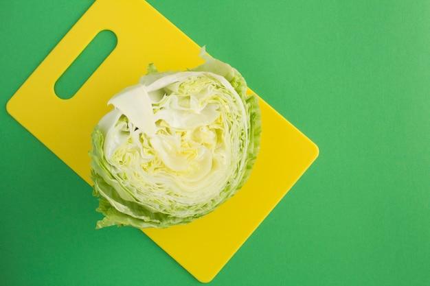 Iceberg de chou tranché sur une planche à découper jaune sur la surface verte. vue de dessus. copiez l'espace.