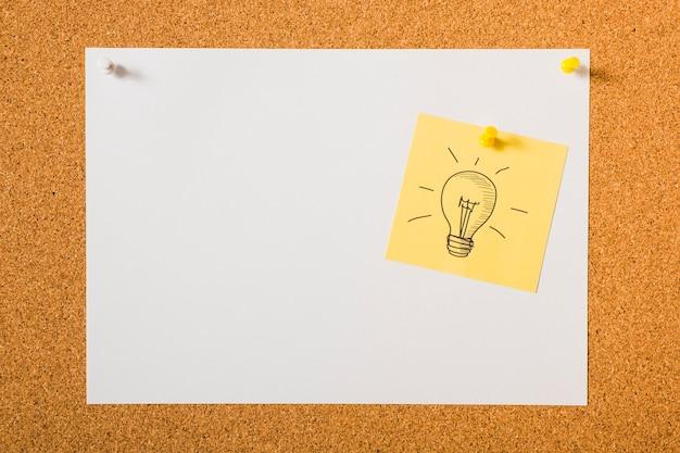 Icône dessinée ampoule sur note collante jaune sur le tableau d'affichage