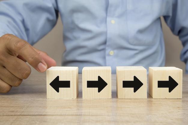 Icône de flèche sur bloc de jouet en bois cube pointant vers des directions opposées.