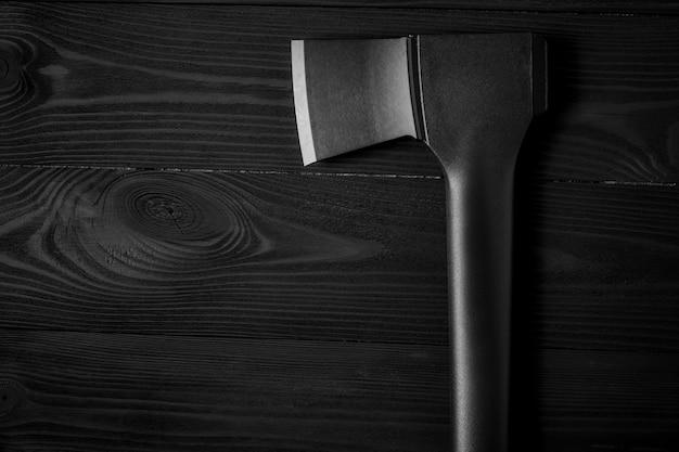 Icône de hache plate isolée sur un fond en bois noir