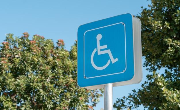 Icône handicapée sur le sol de la réserve de stationnement pour personnes handicapées dans une station d'essence urbaine